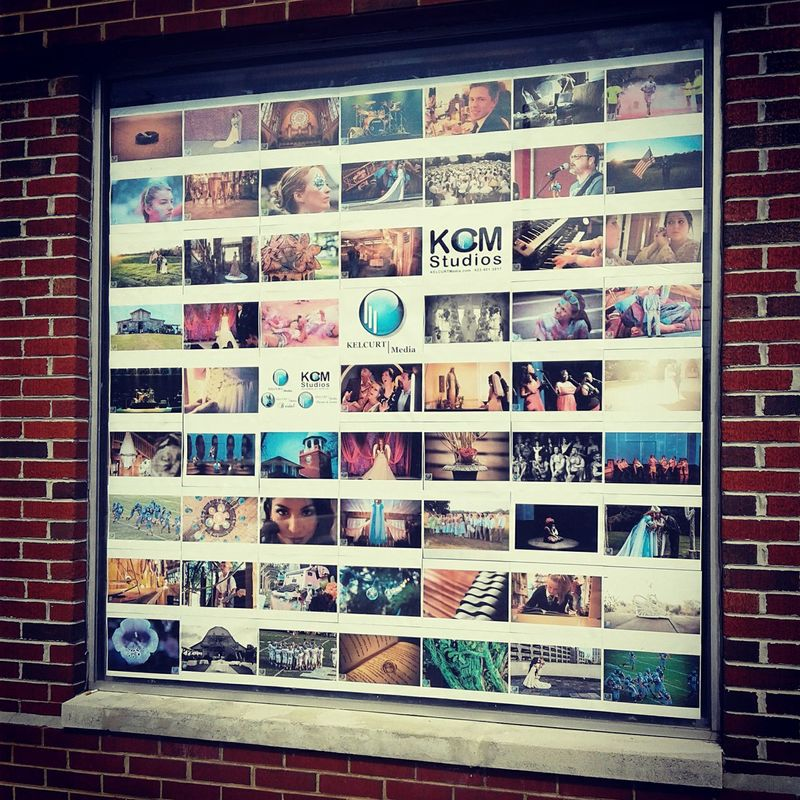 Photo of our window display at KCM Studios showing a grid style layout of 60 photographic images and 3 company logos